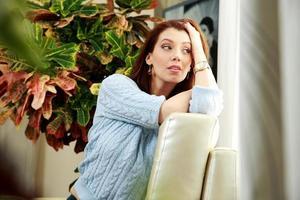 pensativa mujer sentada en el sofá foto