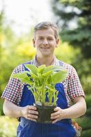 Retrato de jardinero feliz celebración de planta en maceta en vivero