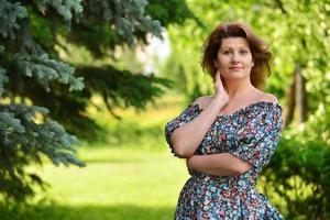 mujer en un vestido con hombros abiertos en bosque de pinos foto