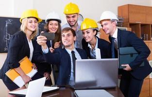 equipe de engenheiros posando e fazendo selfie