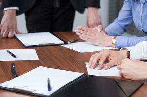 mãos e pranchetas durante reunião de negócios