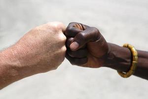 saudação de mão entre um caucasiano e um africano