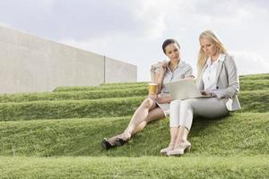 Businesswomen looking at laptop while sitting on grass steps