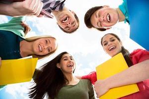 groep lachende studenten bij elkaar blijven en camera kijken