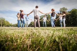 Group of friends at park holding hands. View from below photo