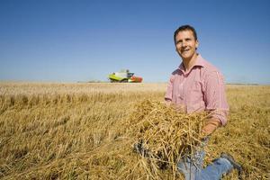 Farmer picking up straw
