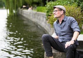 hombre sentado junto al agua foto