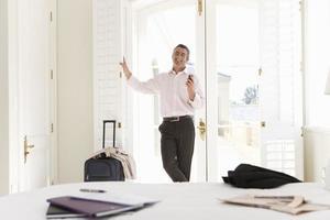 volwassen zakenman permanent door raam, met mobiele telefoon, smi