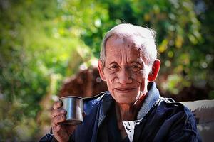 aged cheerful old man holding  cup of coffee photo
