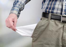 homem mostrando seu bolso vazio no fundo brilhante