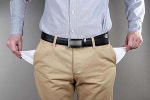 Man showing his empty pockets on grey background