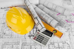 Yellow helmet, calculator, level and project drawings photo