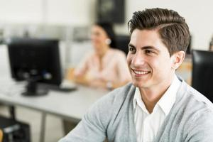 joven guapo estudiando tecnología de la información en un aula