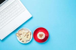 taza de capuchino con forma de corazón y galletas foto
