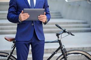 Buen hombre sosteniendo portátil cerca de bicicleta foto