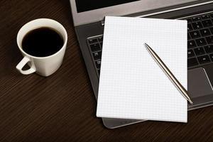 notebook, pen op laptop naast kopje koffie.