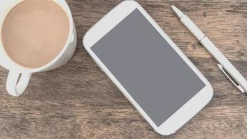White smart phone  and cup of coffee photo