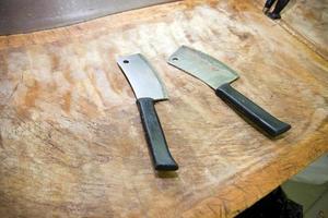 cuchillo de carnicero en la tabla de cortar en la tienda foto
