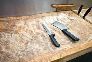 cuchillo de carnicero en la tabla de cortar en el supermercado foto