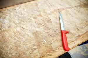 cuchillo de cocina en tabla de cortar de madera en la tienda foto