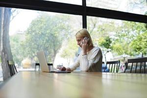 Empresaria en su computadora portátil mientras habla por teléfono inteligente