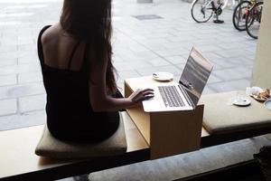 jovem mulher trabalhando no computador portátil durante o almoço