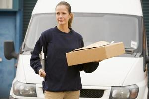 Delivery person standing with van, clipboard and box