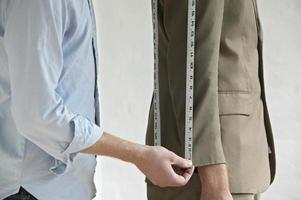 Midsection Of Tailor Measuring Customer's Suit