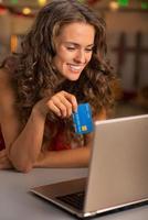 Retrato de mujer joven feliz con tarjeta de crédito usando laptop