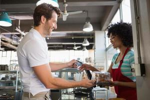 cliente sorridente, pagando com cartão de crédito