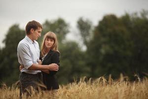 joven hombre y mujer caminando en un campo de trigo