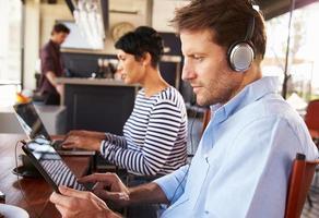 hombre y mujer usando computadoras portátiles en un restaurante foto