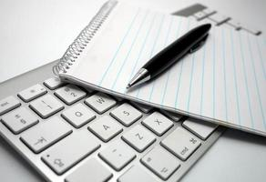 pen and white notepad on keyboard photo