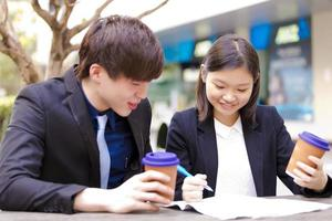 Young female and male Asian business executive using tablet