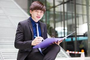 Young Asian male business executive holding file