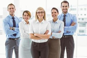 Young business people with arms crossed in office photo