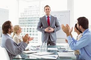 Business people clapping hands in board room meeting photo