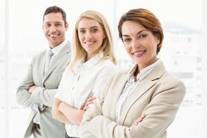 Happy business people with arms crossed in office photo