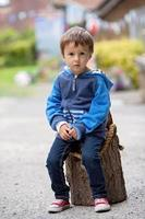Portrait of a boy, sitting on a tree trunk photo