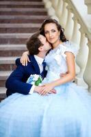 happy husband kisses his wife on the stairs