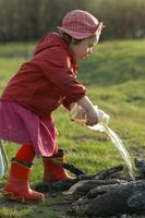 Three year old girl pours water fire