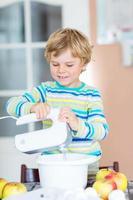 Chico rubio chico divertido hornear tarta de manzana en el interior