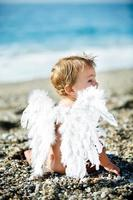 lindo niño sentado en la playa foto