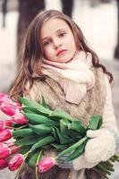 Retrato vertical de niña adorable niño con tulipanes rosados