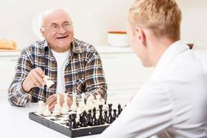 Grandson and grandfather playing chess in kitchen