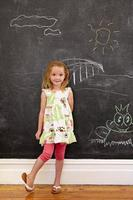 Innocent little girl standing with chalk drawings at home photo