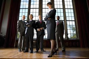 Small group of businessmen and woman in hall of woman