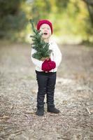 Niña en mitones y gorra con pequeño árbol de Navidad