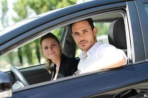 beautiful happy young business people man woman driving rental car