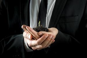 manos del empresario sosteniendo el suelo con brotes jóvenes foto